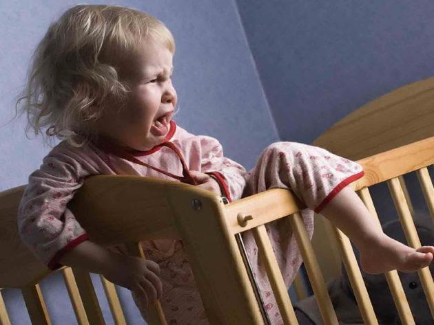 Ребенок плачет и вылезает из кроватки