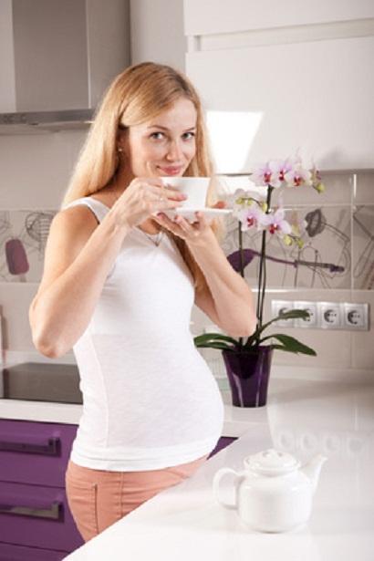 Беременная девушка на кухне с чашкой чая