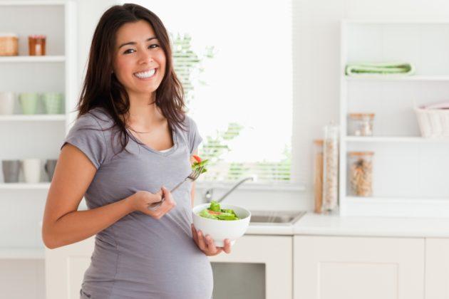 Беременная женщина с чашкой салата в руках