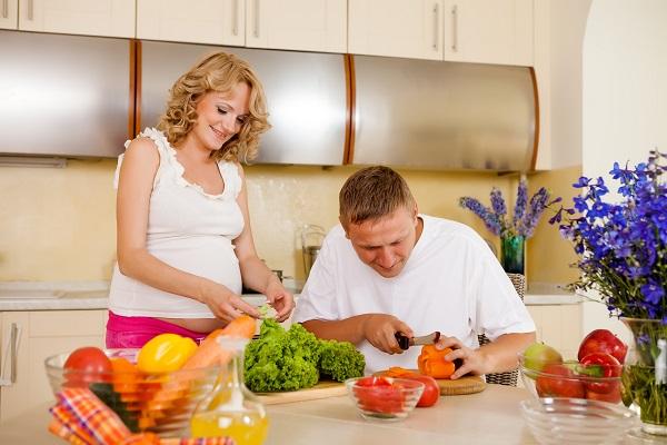 Беременная женщина и её супруг готовят овощи