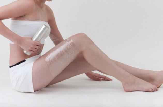 Девушка делает обёртывание на ноге