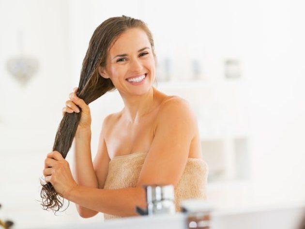 Довольная девушка держит в руках свои волосы
