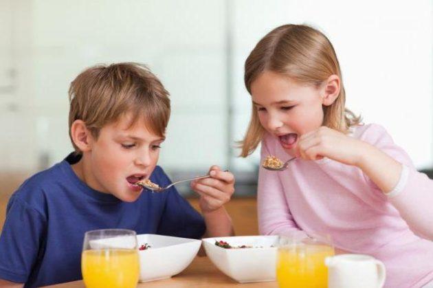 Дети едят смесь из кукурузных хлопьев и фруктов