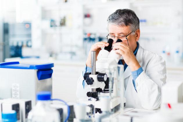 Учёный смотрит в микроскоп