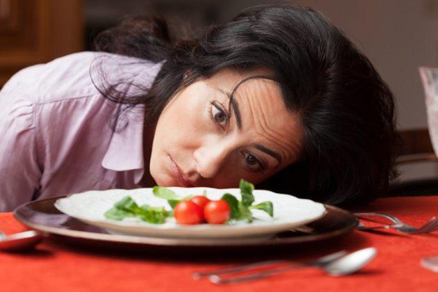 Измождённая девушка перед тарелкой