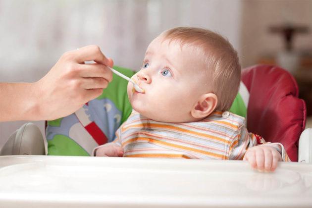 Ребёнка кормят с ложки