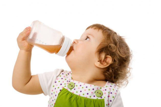Ребенок пьет сок мандарина