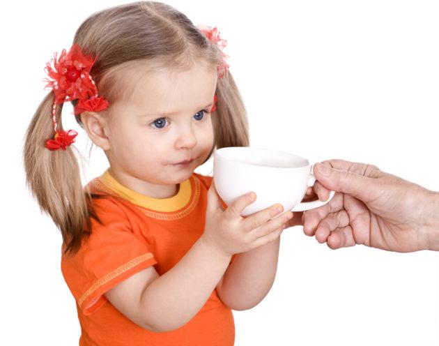 Девочке дают чашку с чаем