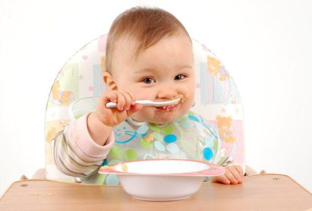 Ребёнок ест кашу за столиком