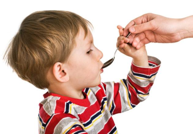 Ребёнок принимает сироп из ложки