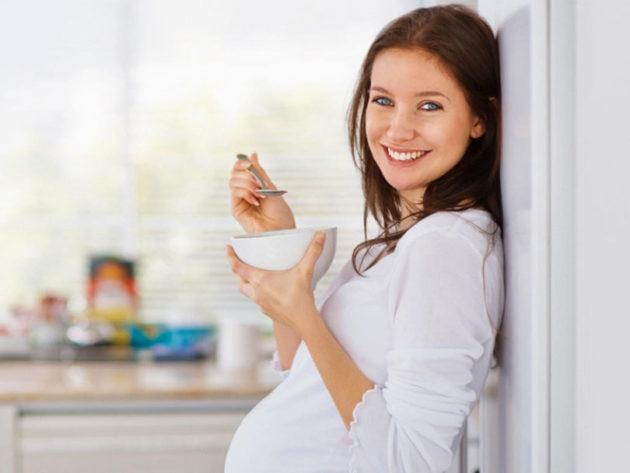 Беременная девушка ест творог