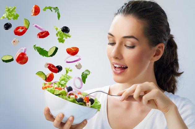 Девушка держит чашу с овощным салатом