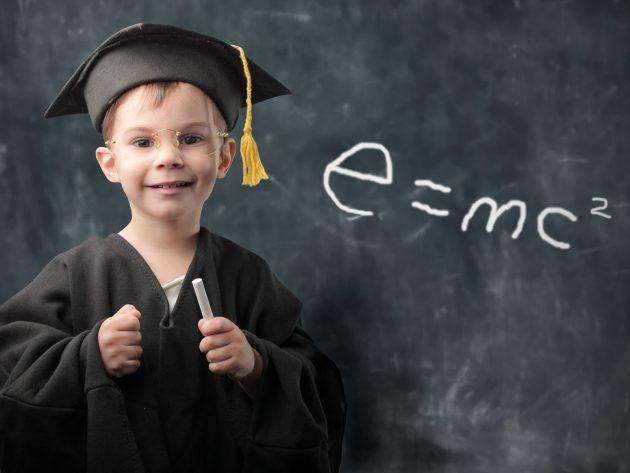 Довольный маленький мальчик у школьной доски