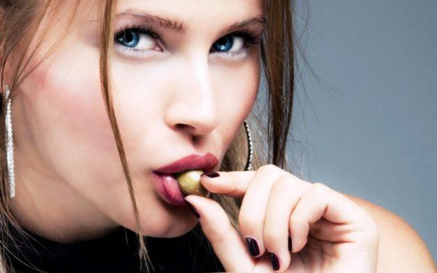 Девушка ест оливку