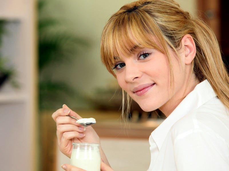 Девушка кушает йогурт