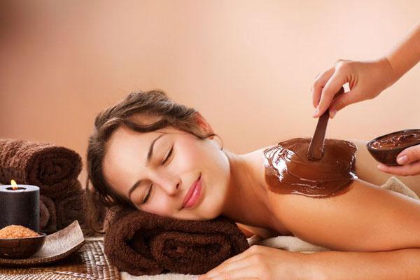 Девушке наносят шоколад на кожу