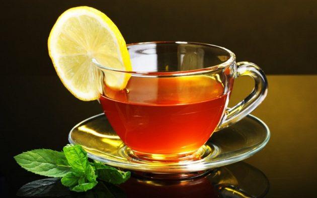 Чёрный чай с лимоном в стеклянной чашке