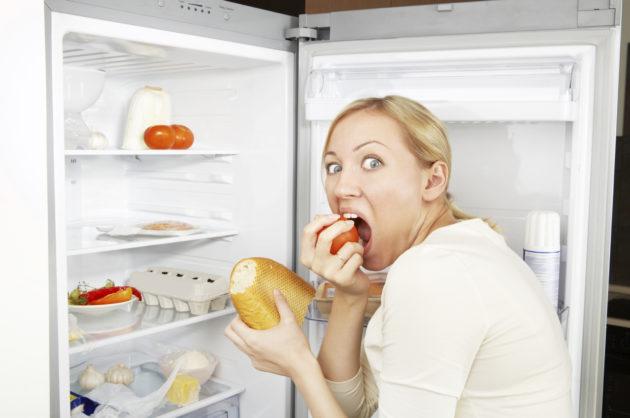 Девушка жадно ест перед холодильником