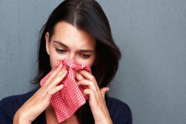 Простуженная девушка в синей кофте, сморкающаяся в клетчатый платок, на сером фоне