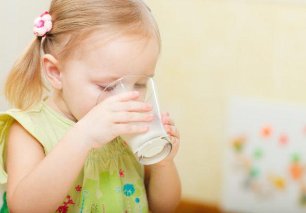 Маленькая девочка пьет кефир из прозрачного стакана