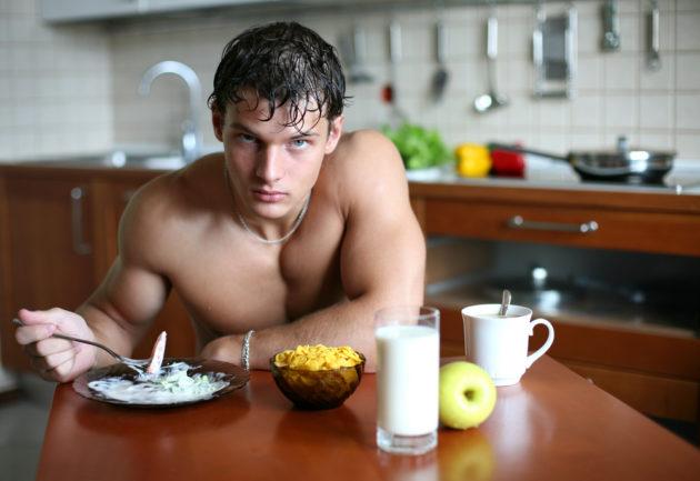 Обнажённый парень сидит за обеденным столом на кухне