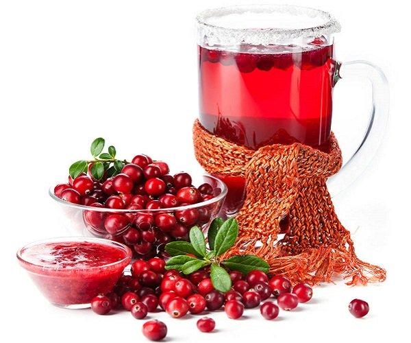 Стакан брусничного чая и ягоды